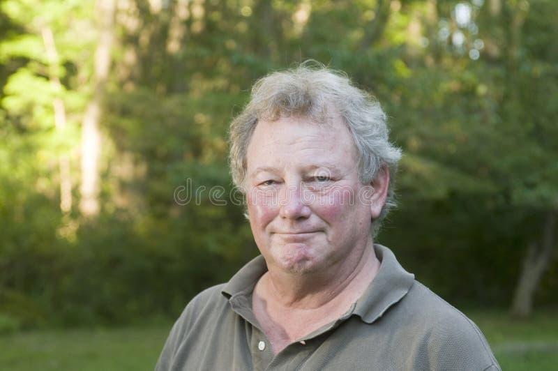 Homem sênior da Idade Média no quintal suburbano fotos de stock