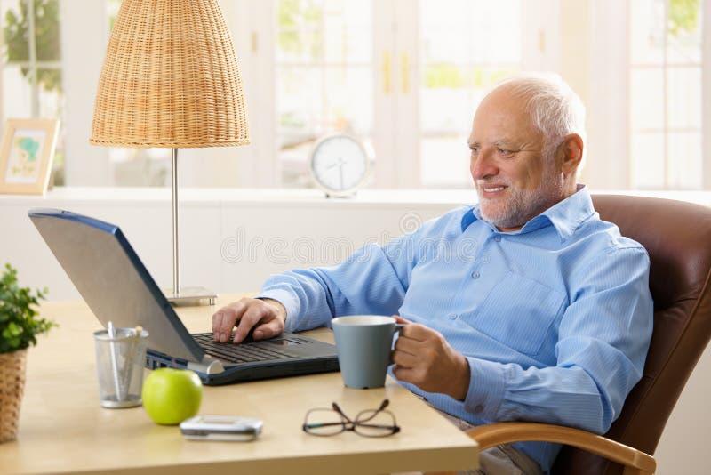 Homem sênior de sorriso que usa o portátil