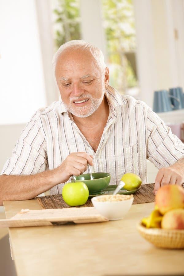 Homem sênior feliz que come o chá na cozinha imagens de stock royalty free