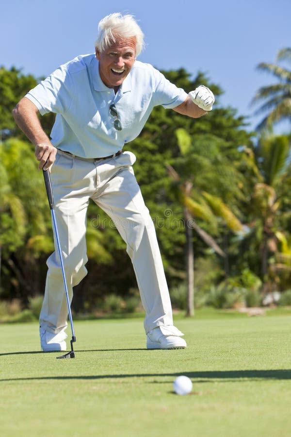 Homem sênior feliz que põr jogando o golfe foto de stock royalty free