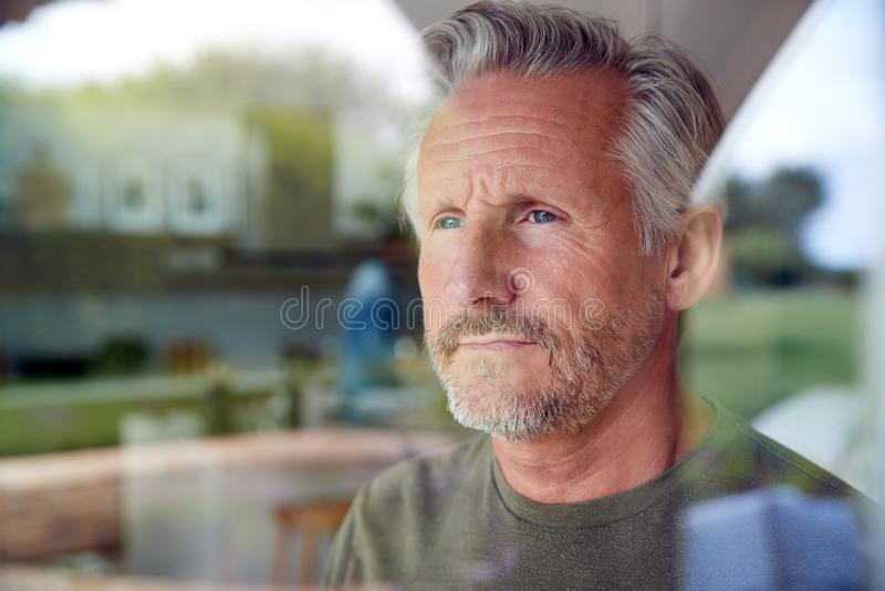 Homem Sênior Interessado Em Pé E Olhando Para Fora Da Porta Da Cozinha Exibido Através Da Janela imagem de stock