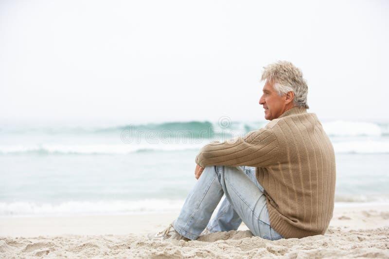 Homem sênior no feriado que senta-se na praia do inverno fotografia de stock royalty free