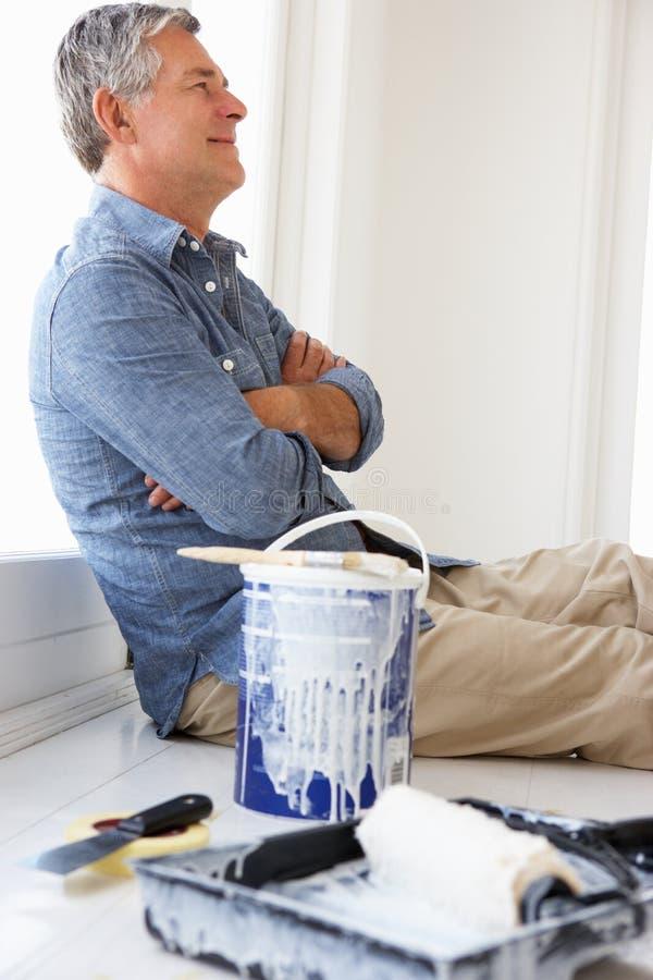 Homem sênior que decora a casa fotos de stock