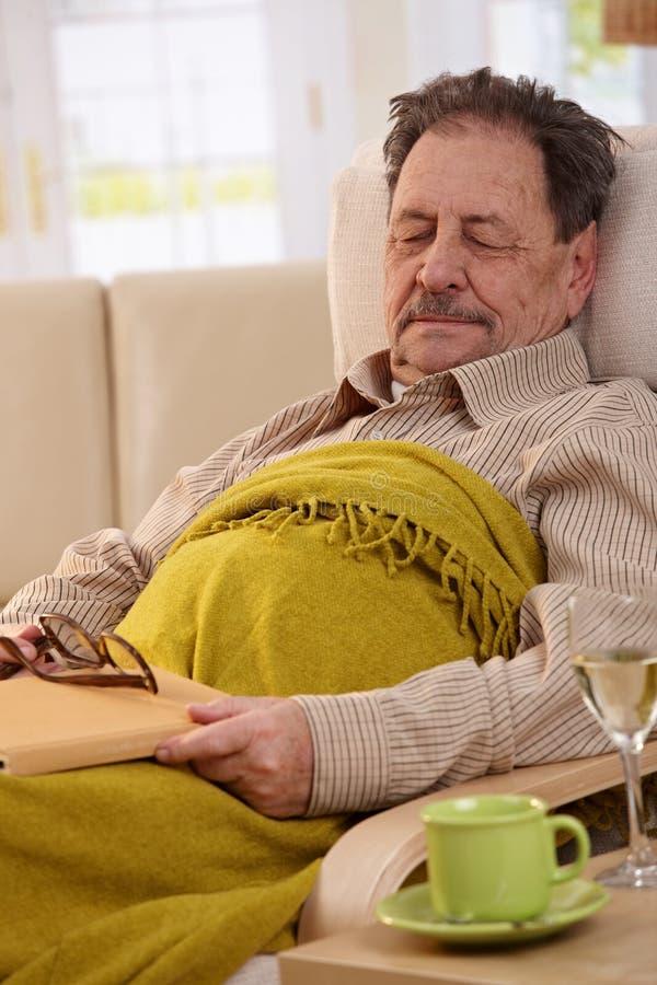 Homem sênior que dorme na poltrona foto de stock royalty free