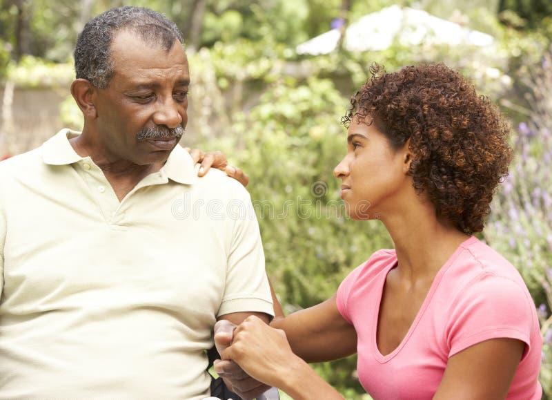 Homem sênior que está sendo consolado por Adulto Filha fotos de stock royalty free