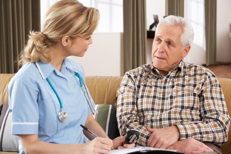Homem sênior que fala ao visitante da saúde fotografia de stock