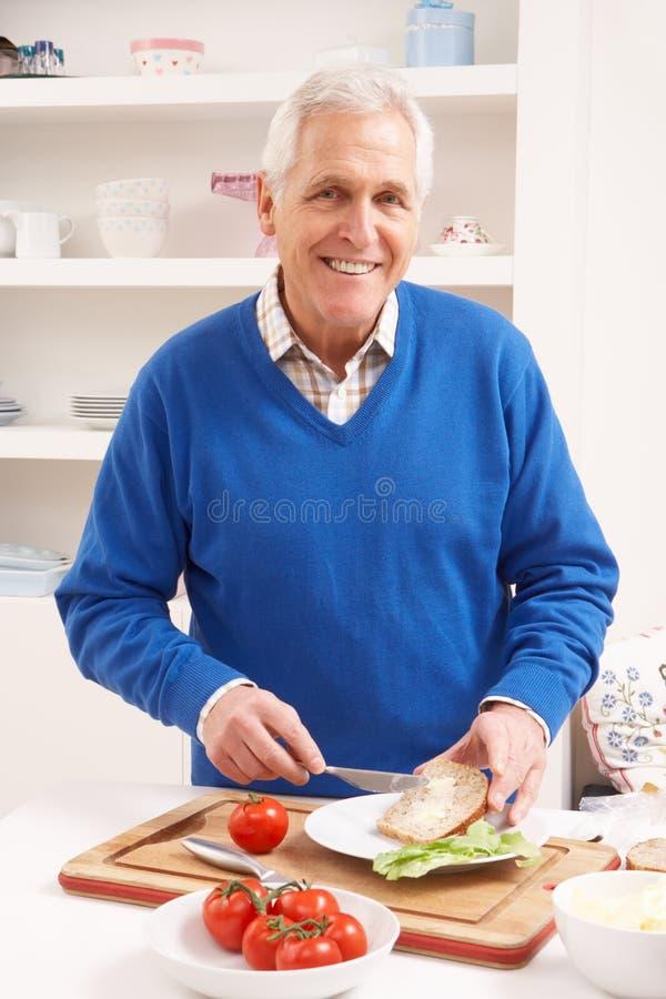 Homem sênior que faz o sanduíche na cozinha fotografia de stock royalty free