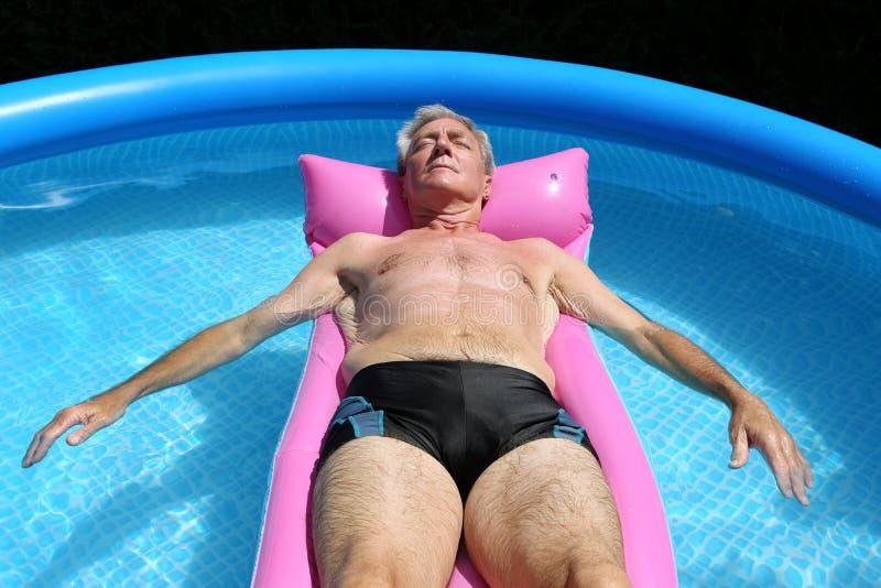 Homem sênior que flutua em um lilo fotos de stock royalty free