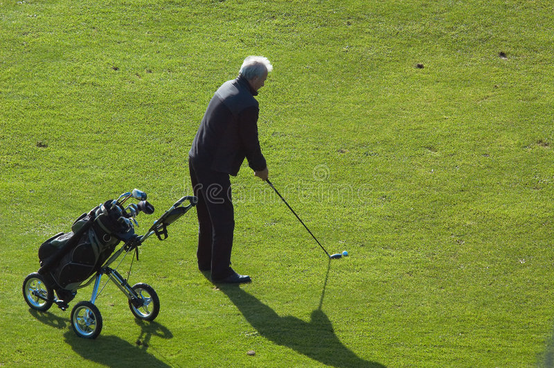 Homem sênior que joga o golfe foto de stock