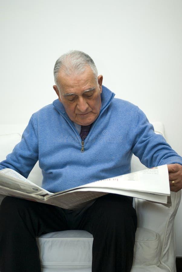 Homem sênior que lê o jornal foto de stock