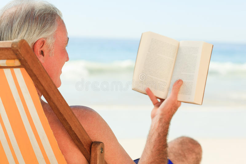Homem sênior que lê um livro imagem de stock