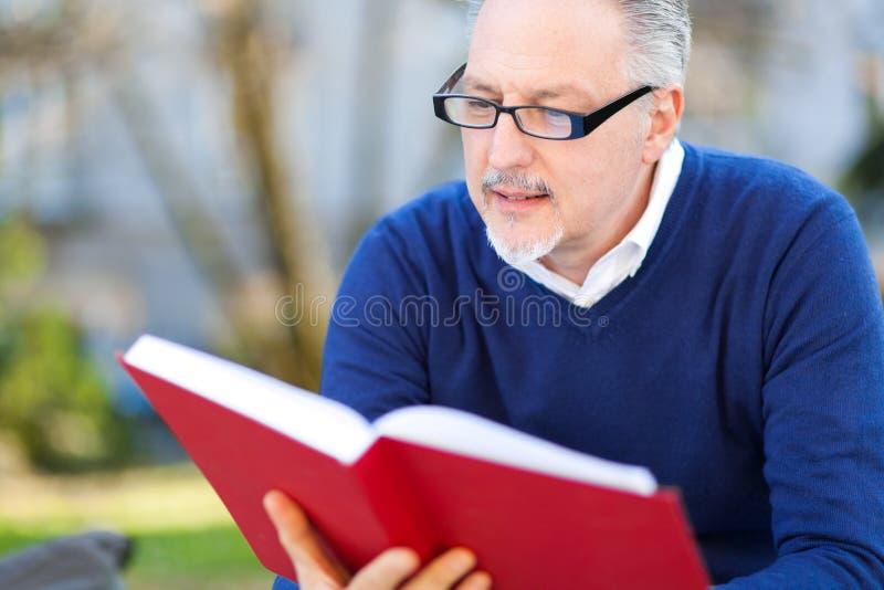 Homem sênior que lê um livro fotografia de stock