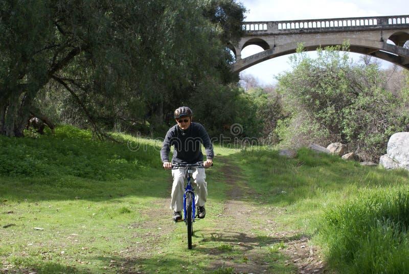 Homem sênior que monta uma bicicleta foto de stock