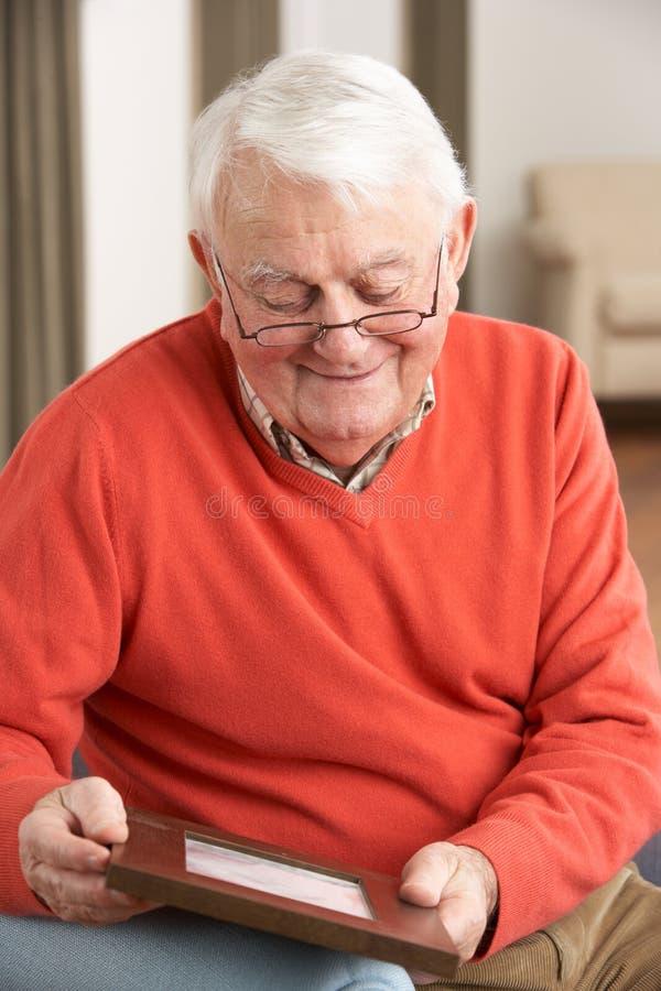 Homem sênior que olha a fotografia no frame foto de stock royalty free