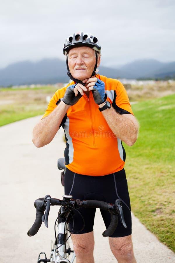 Homem sênior que põr sobre o capacete de ciclagem imagens de stock royalty free
