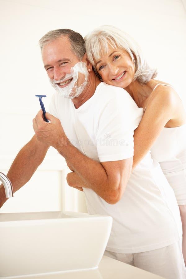 Homem sênior que raspa no espelho do banheiro com esposa fotos de stock