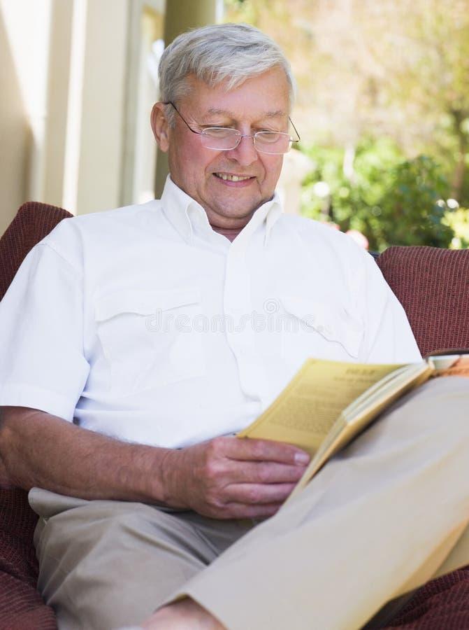 Homem sênior que relaxa com livro imagens de stock royalty free