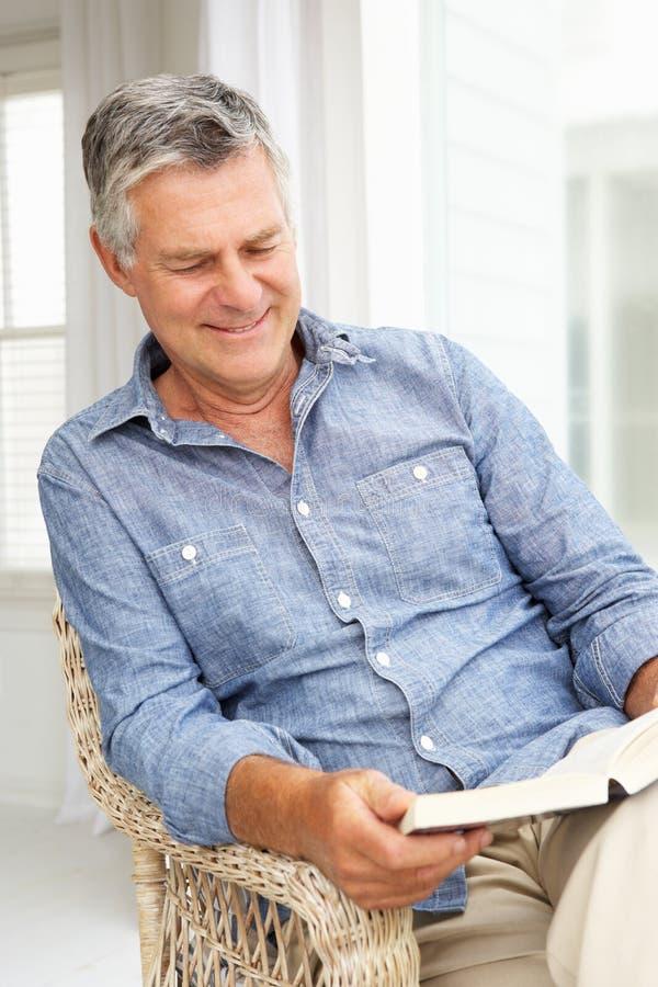 Homem sênior que relaxa em casa com um livro imagem de stock