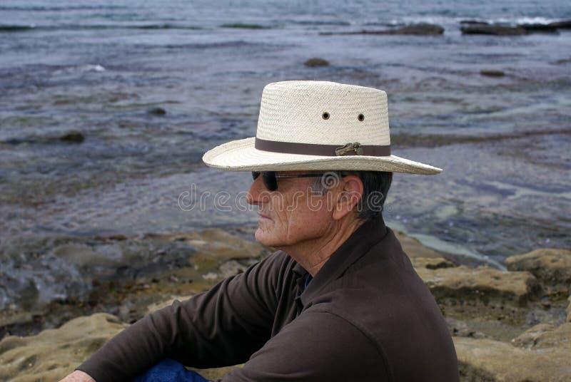 Homem sênior que senta-se sozinho por Oceano foto de stock royalty free