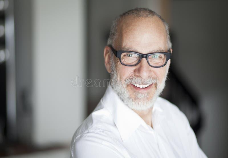 Homem sênior que sorri na câmera imagens de stock royalty free