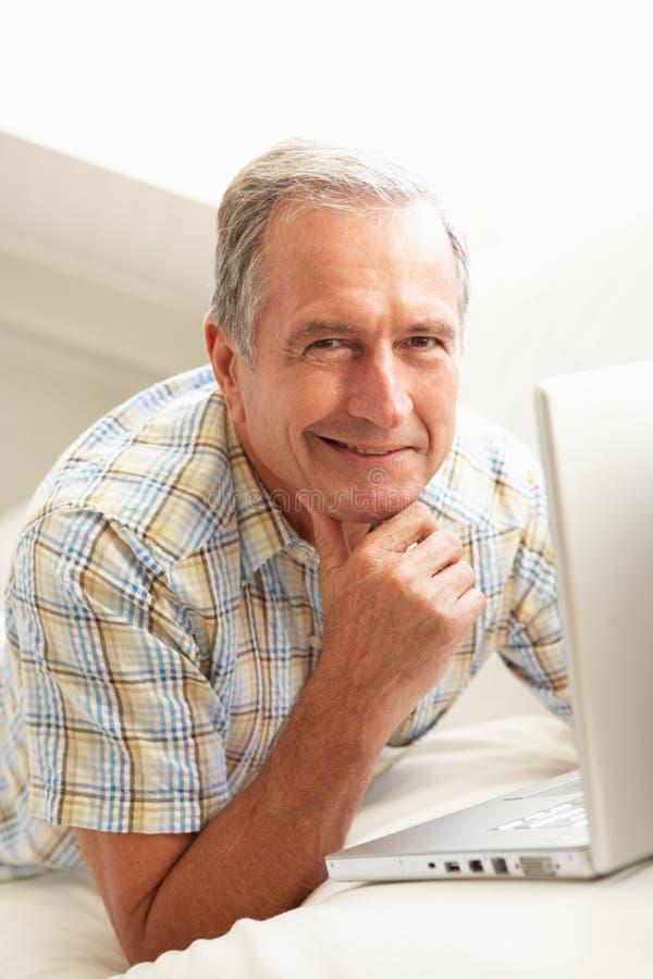 Homem sênior que usa o assento de relaxamento do portátil no sofá fotos de stock
