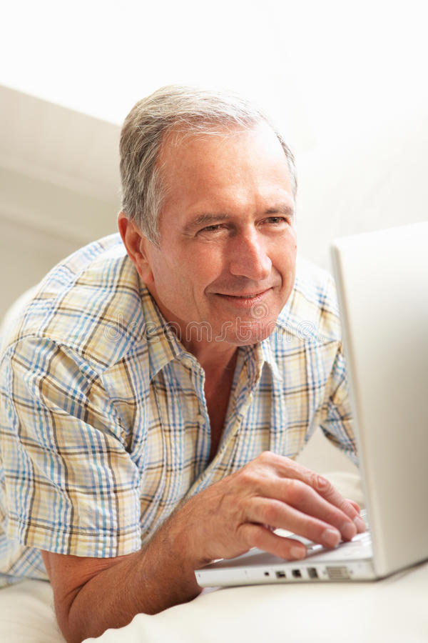 Homem sênior que usa o assento de relaxamento do portátil no sofá fotos de stock royalty free