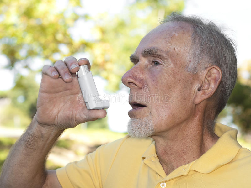 Homem sênior que usa o inalador da asma ao ar livre imagens de stock