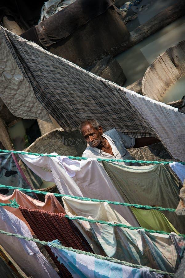 Homem sênior que verific a lavanderia India imagem de stock