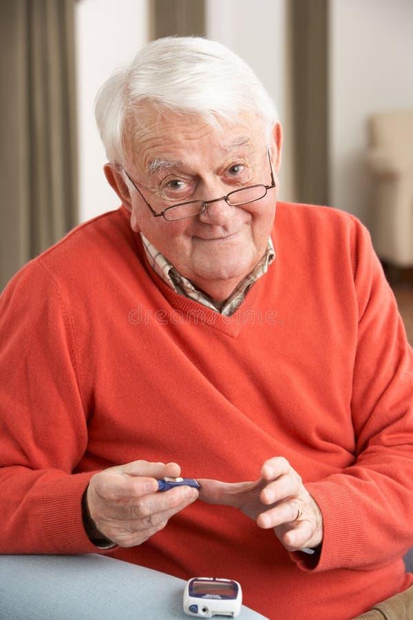 Homem sênior que verific o nível de açúcar de sangue em casa imagem de stock