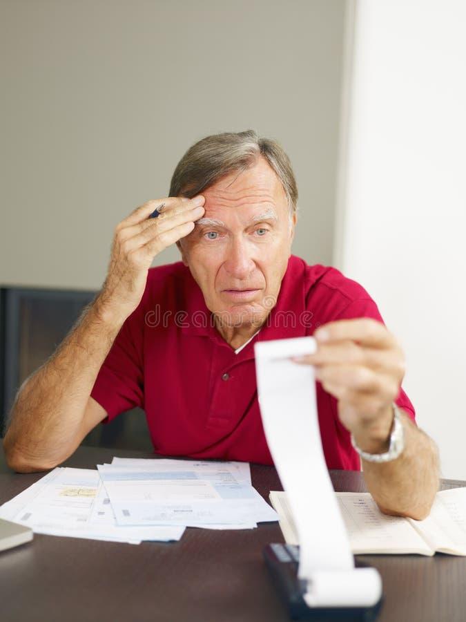Homem sênior que verific para casa finanças foto de stock royalty free