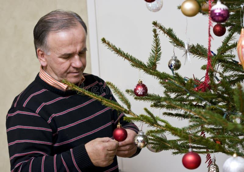 Homem sênior que veste a árvore de Natal imagem de stock