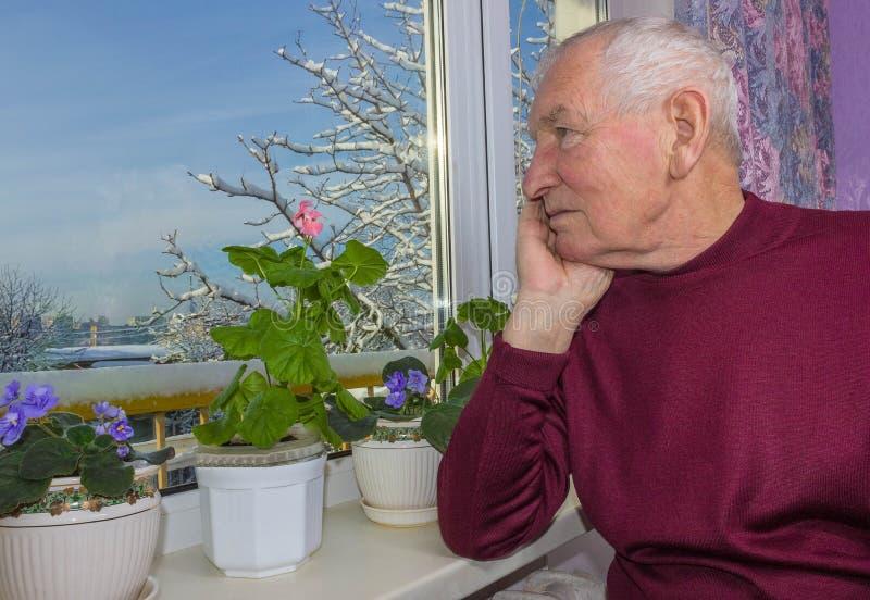 Homem só idoso que senta-se perto da janela em sua casa imagem de stock