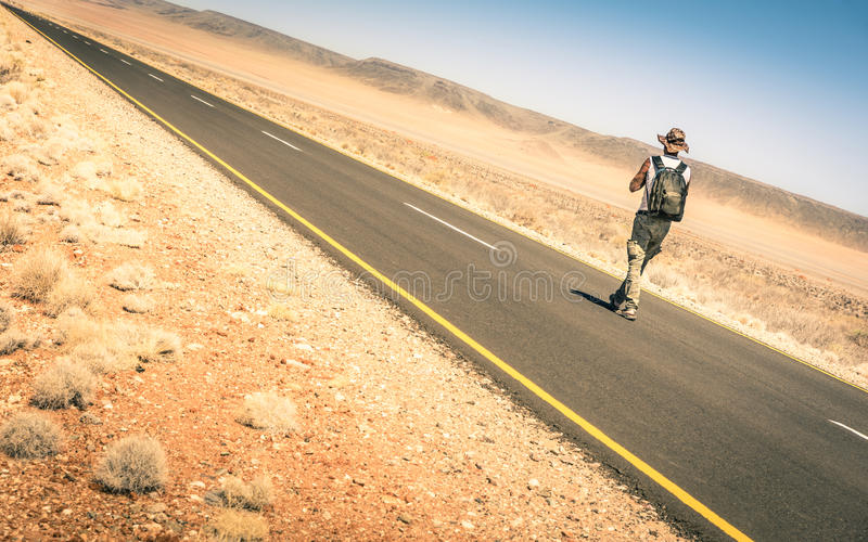 Homem só que anda ao longo da estrada no deserto africano namibiano imagens de stock royalty free