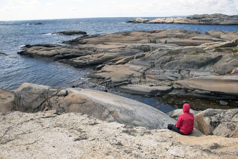 Homem só que senta-se na rocha e que olha no mar foto de stock royalty free
