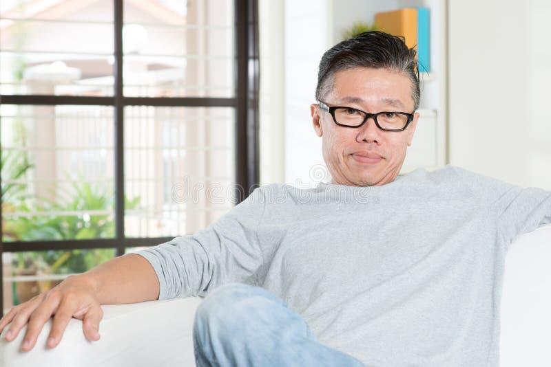 Homem 50s asiático maduro que senta-se em casa fotografia de stock