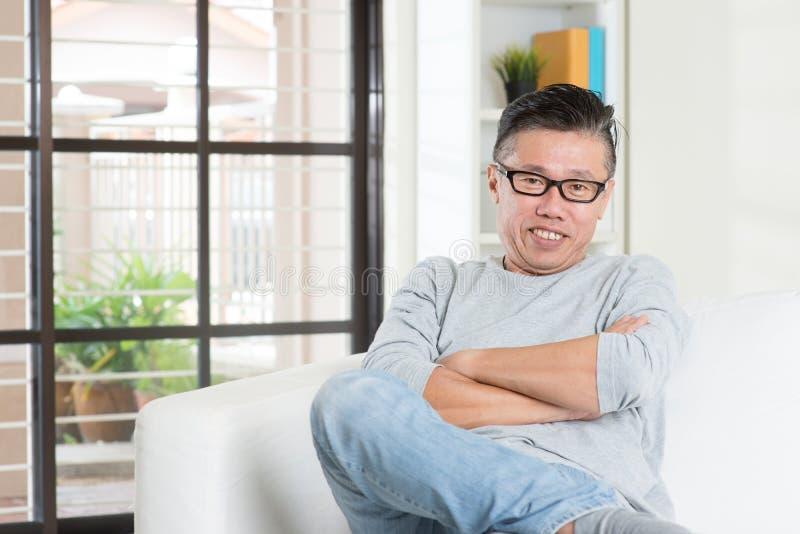 Homem 50s asiático maduro que senta-se em casa imagens de stock