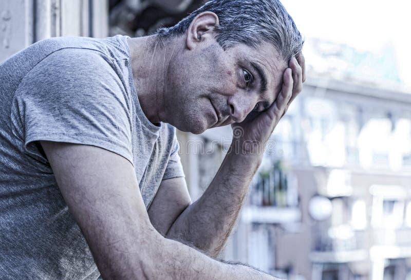 Homem 40s triste e deprimido que olha com o balco do ar livre em casa fotografia de stock royalty free