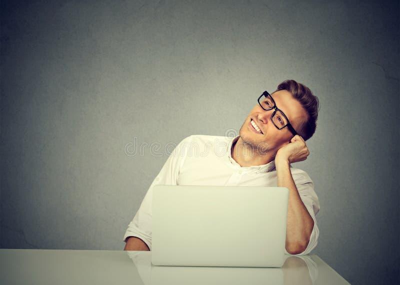 Homem satisfeito com o portátil que olha afastado sonhadoramente imagens de stock royalty free
