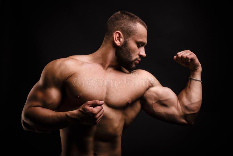 Homem saudável dos esportes com músculos grandes em um fundo preto Atleta que mostra fora o bíceps e o tríceps Conceito do halter imagem de stock royalty free