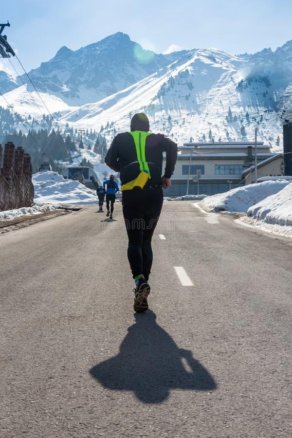 Homem saudável novo do esporte que corre na estrada asfaltada em montanhas da neve no exercício duro do corredor da fuga na energ fotos de stock royalty free