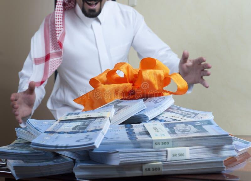 Homem saudita surpreendido com as pilhas de dinheiro na tabela fotos de stock