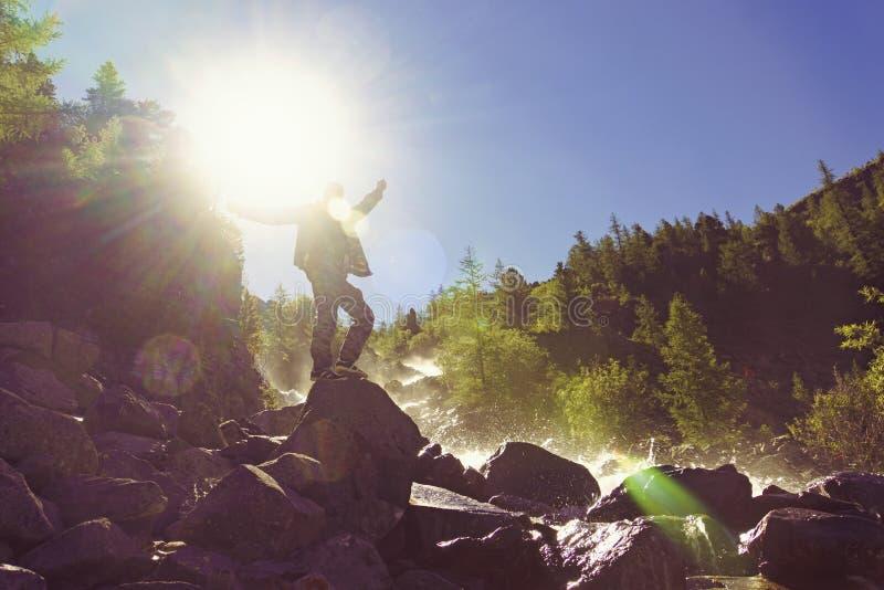 homem se levanta sobre um penhasco trópico surpreendente vista maravilhosa de montanhas sobre águas-cegas verdes e levantou as mã foto de stock royalty free