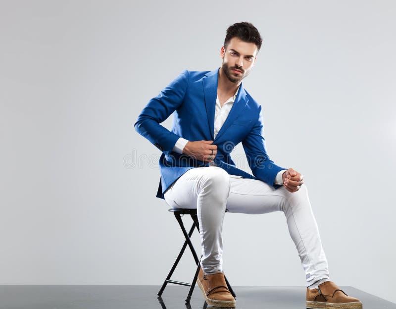 Homem sedutor no terno azul que senta-se na cadeira de madeira imagens de stock