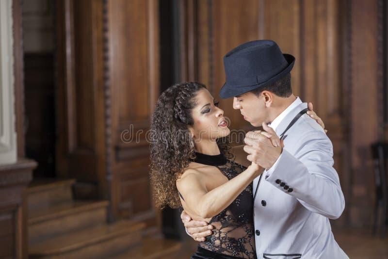 Homem seguro e sócios fêmeas que executam o tango imagens de stock