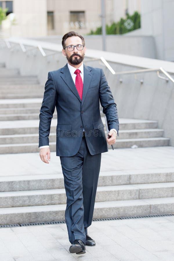 Homem seguro no terno elegante que anda e que olha sério imagem de stock royalty free