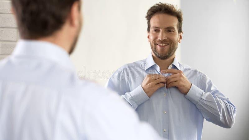 Homem seguro que abotoa sua camisa no humor otimista, preparando-se para o trabalho imagem de stock