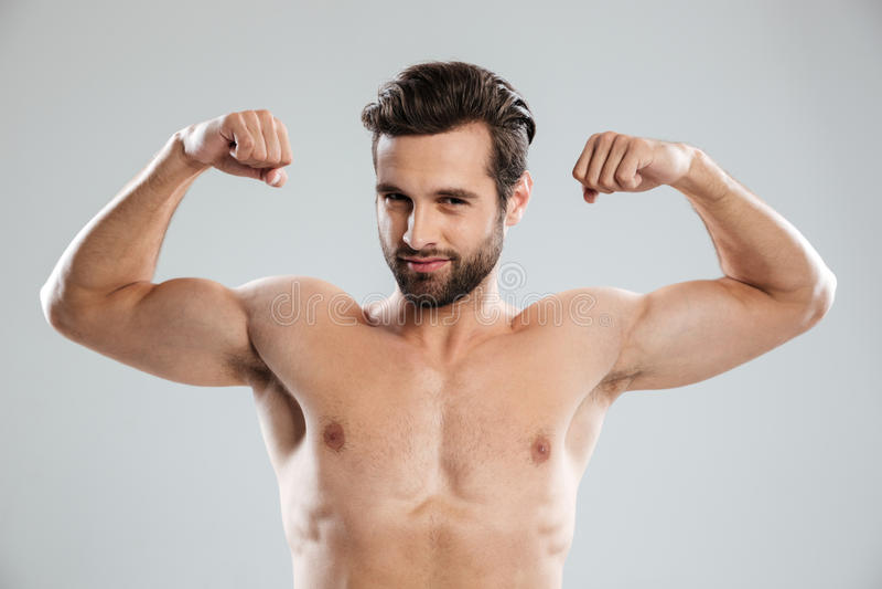 Homem seguro que mostra seu bíceps e que olha a câmera imagens de stock