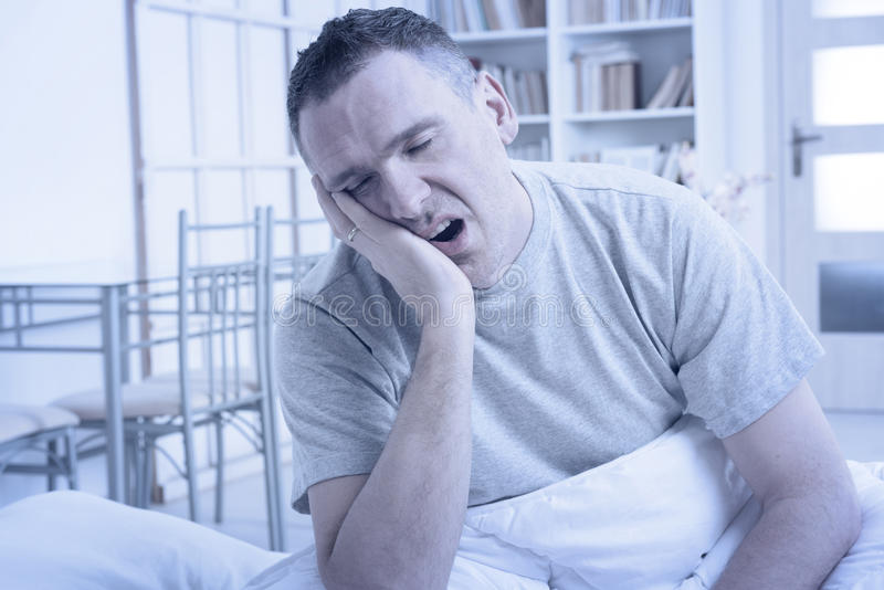 Homem sem sono na cama foto de stock royalty free