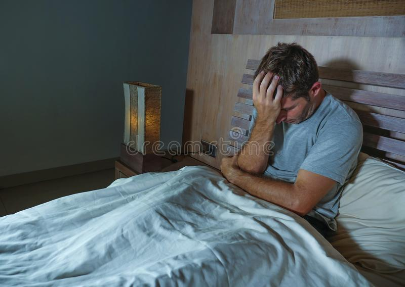 Homem sem sono triste e deprimido novo que encontra-se no sentimento em casa preocupado e pensativo da cama do quarto do sofrimen foto de stock royalty free