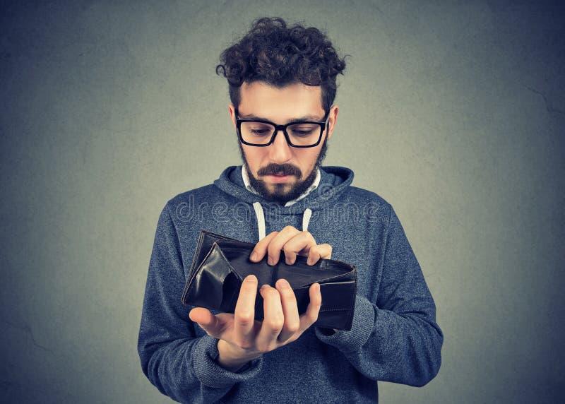 Homem sem a terra arrendada de dinheiro uma carteira vazia fotografia de stock royalty free